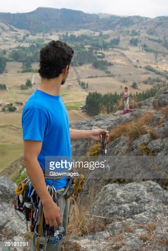 Male rock climber looking at a female rock climber standing on a rock : Foto de stock