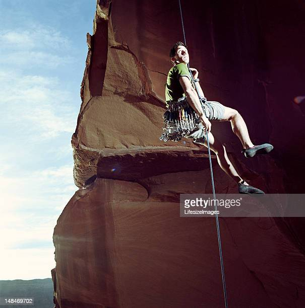 Male rock climber rappelling, low angle view, Moab, Utah, USA