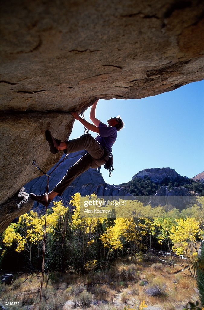 Male rock climber scaling overhang : Stock Photo