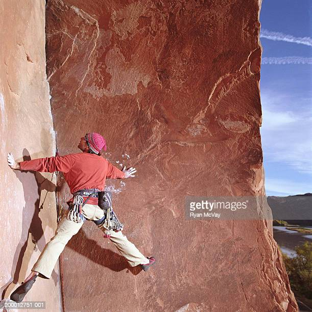 Male rock climber scaling sheer sandstone rock face, rear view