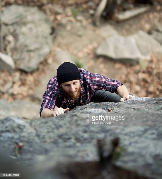 A male rock climber with a beard grimaces while he struggles to grab a hold.