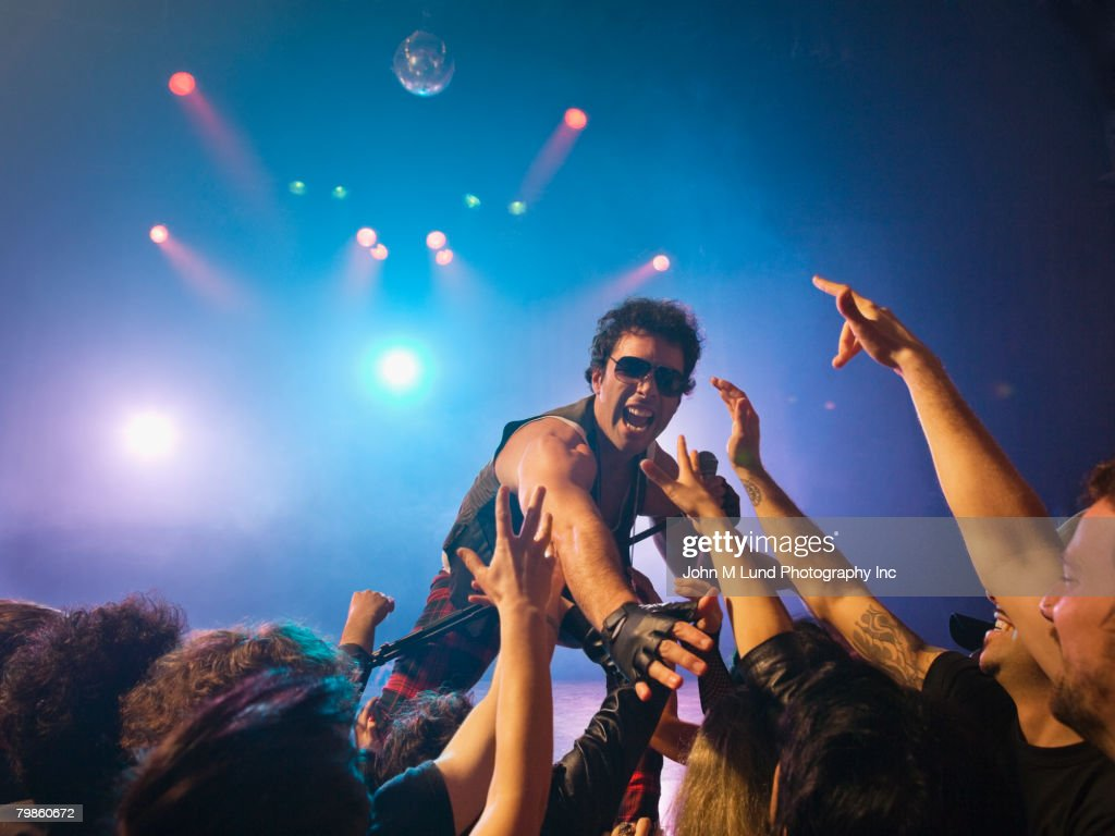 Male rock star on stage interacting with audience : Stock Photo