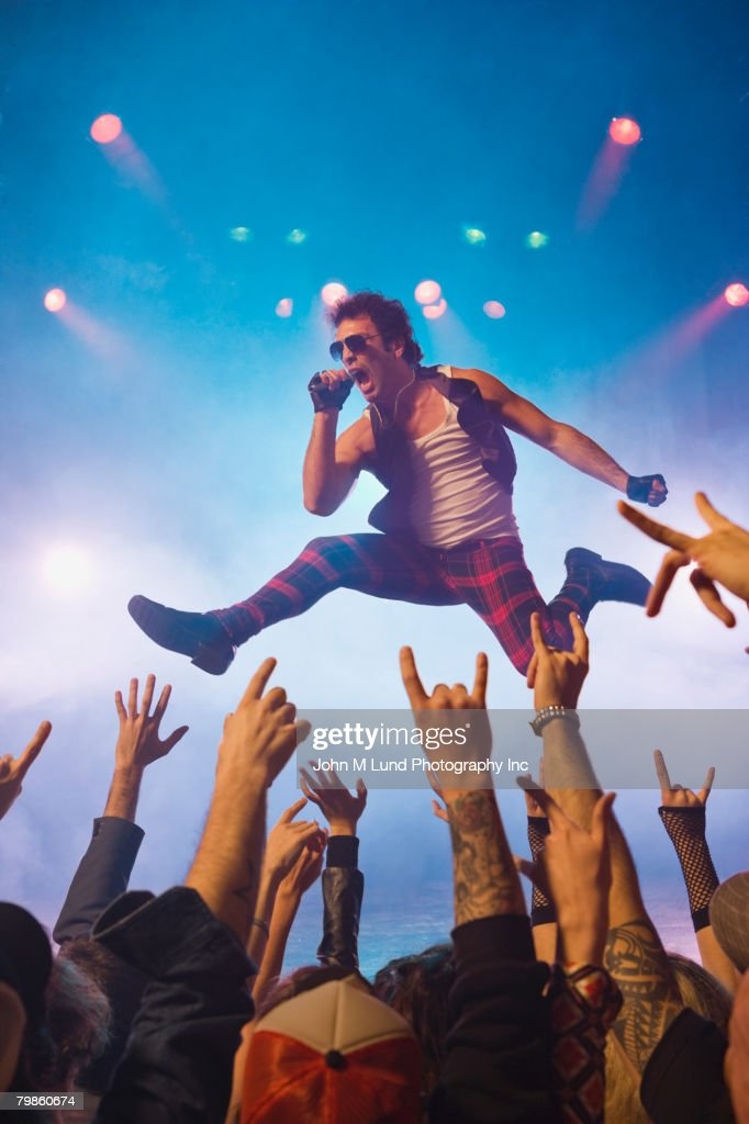 Male rock star performing in front of audience : Stock Photo