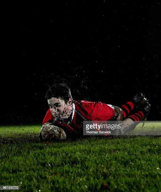 Male rugby player diving with ball scoring try