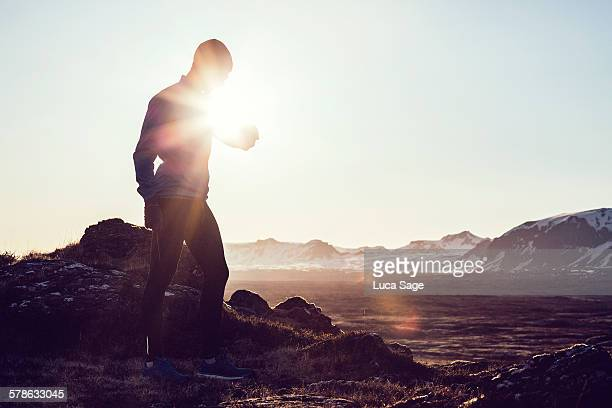Male runner checks his fitness tracker at sunrise