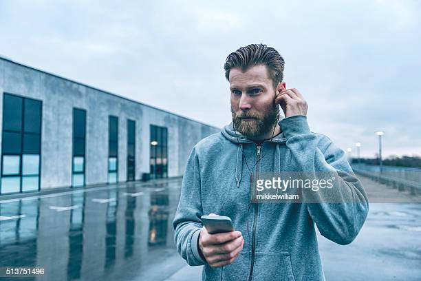 Male runner gets ready for run and listens to music