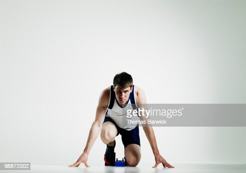 Male runner in starting blocks looking up