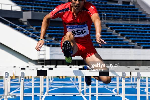 male runner jumping hurdles in race