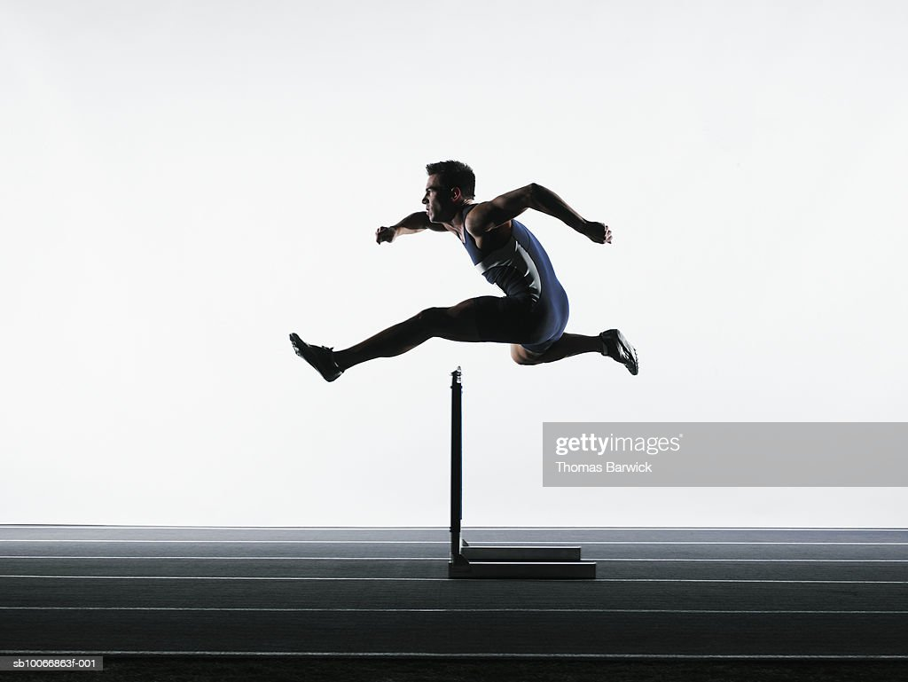 Male runner jumping over hurdle : Stock Photo