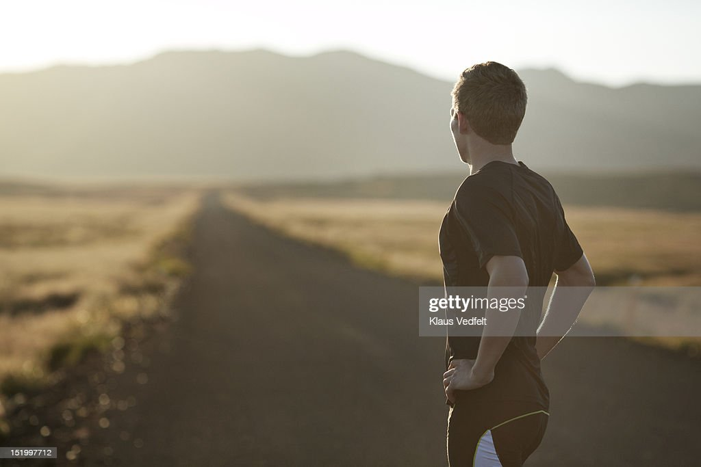 Male runner looking at endless road : Stock Photo