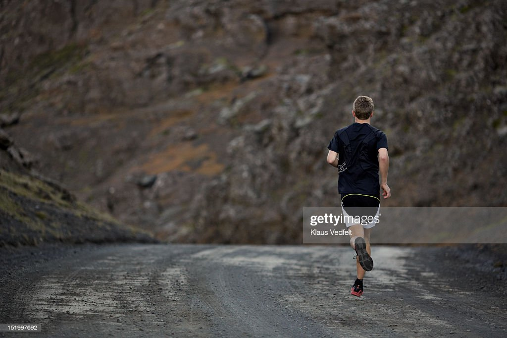 Male runner on mountain road, back view : Stock Photo