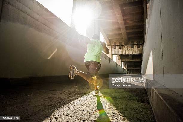 Male runner running under city bridge