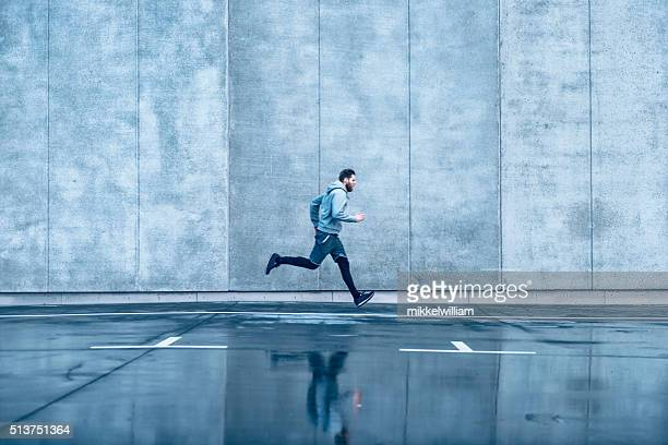 Male runner runs fast in front of concrete building