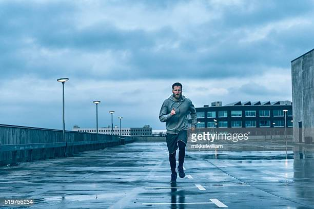 Male runner runs on wet streets after rain