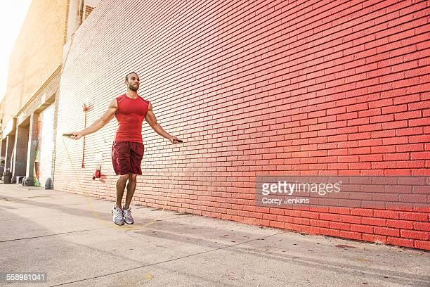 Male runner skipping on sidewalk