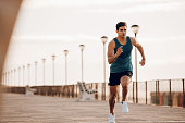 Full length shot of healthy young man running on the promenade. Male runner sprinting outdoors.