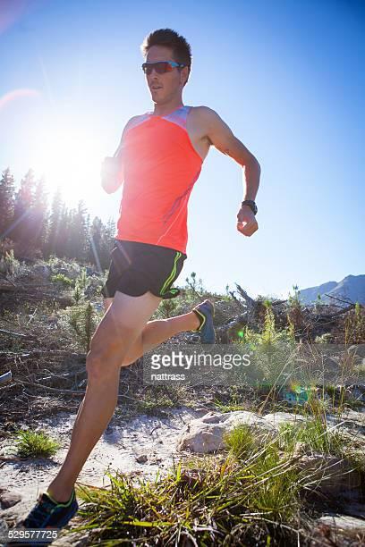 Mâle coureur foulées sur un sentier de montagne