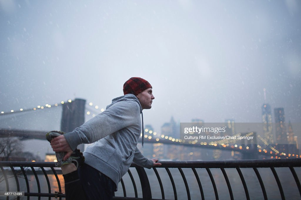 Male runner warming up next to East river, Brooklyn, New York, USA : Stock Photo