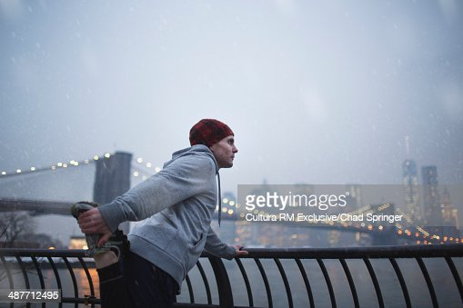 Male runner warming up next to East river, Brooklyn, New York, USA