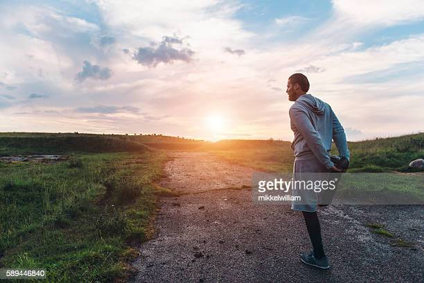 Male runner warms up before sunset run outside
