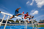 male runners jumping hurdles in race