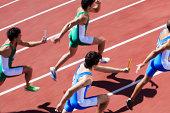 Male runners passing relay baton