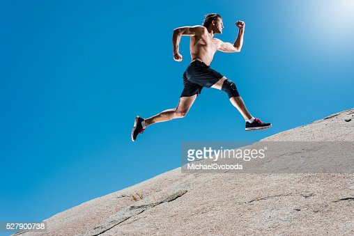 Male Running Up A Granite Boulder In The Mountains