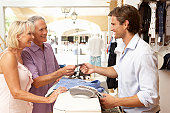 Male Sales Assistant At Checkout Of Clothing Store With Customers