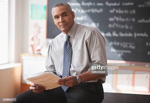 Male school teacher in front of blackboard with papers