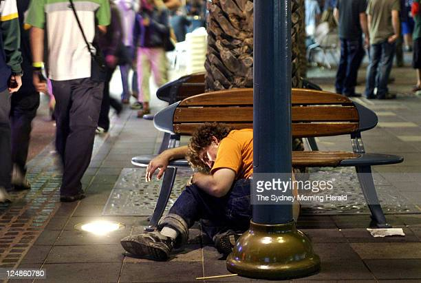 A male schoolie sleeps on the ground supported by a bench as hundreds of schoolies pass him by Thousands of year 12 leavers descend on Surfers...