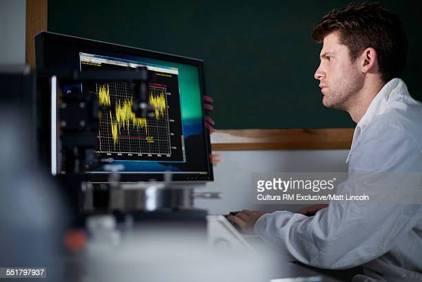 Male science student analyzing results on computer