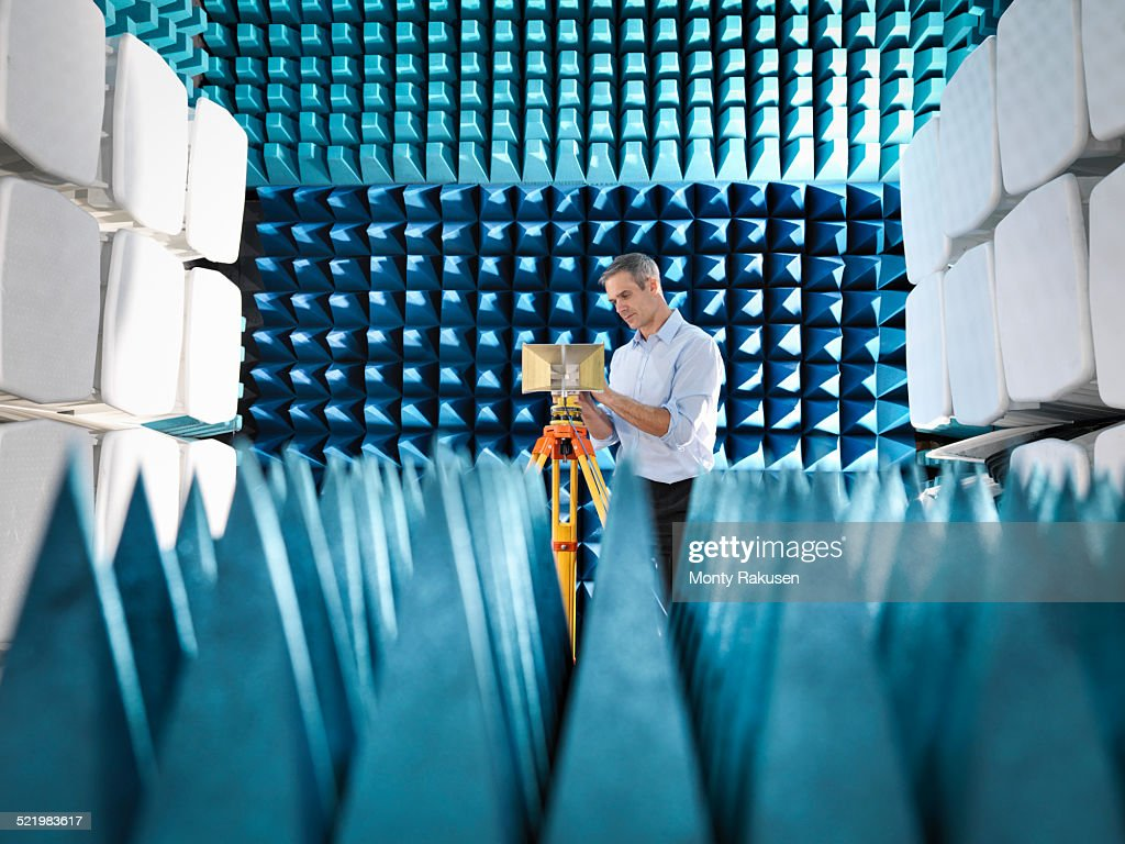Male scientist preparing to measure electromagnetic waves in anechoic chamber