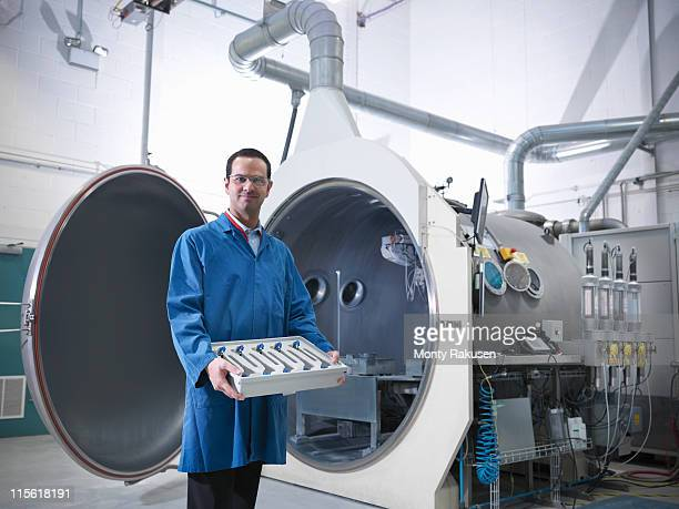 Male scientist with product looking to camera, stood in front of vacuum tank in engineering factory