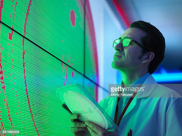 Male scientist with silicon wafer studying graphical display of wafer on screens