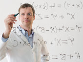 Male scientist working out a formula