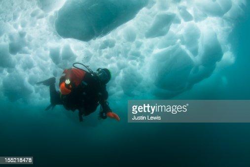 Male scuba diver swimming under an iceberg