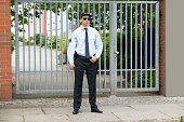 Portrait Of Young Male Security Guard Standing At The Entrance