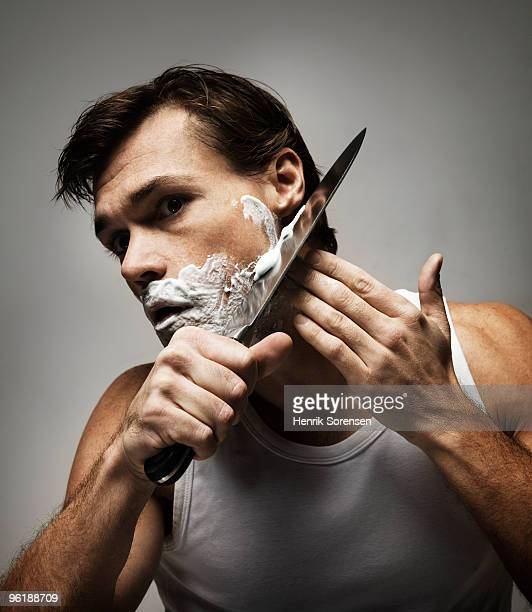 Male shaving with a large kitchen knife