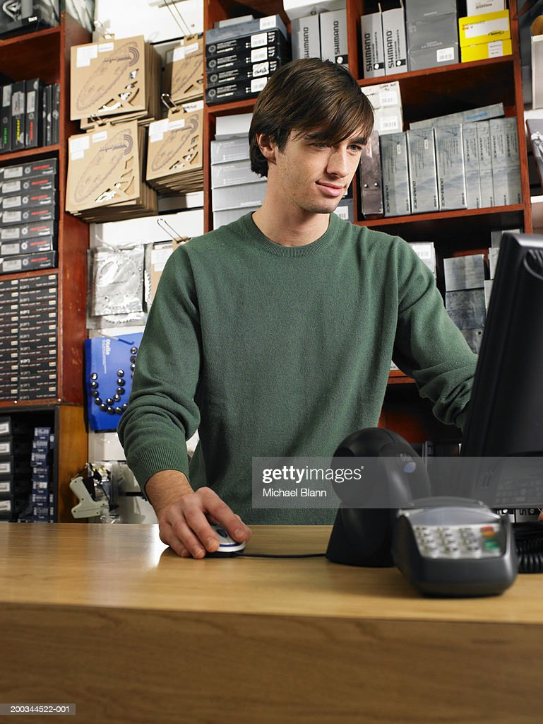 Male shop assisntant using computer, low angle view : Stock Photo