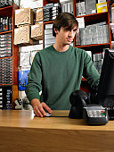 Male shop assisntant using computer, low angle view