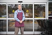 Male shop assistant standing in front of shop doors, portrait