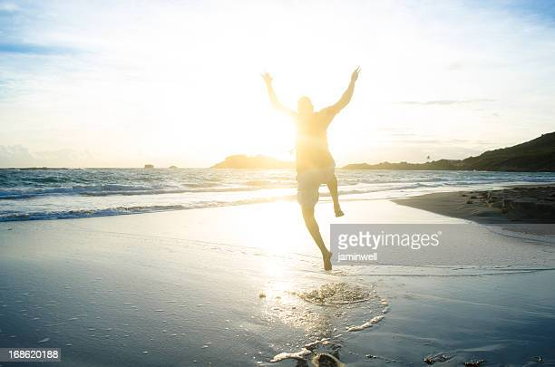 male silhouette jumping at beach against sunrise