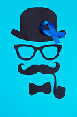 Male silhouette with mustache, glasses and hat patterns and blue ribbon symbol on the blue background. Movember concept. Prostate Cancer and men's health awareness.