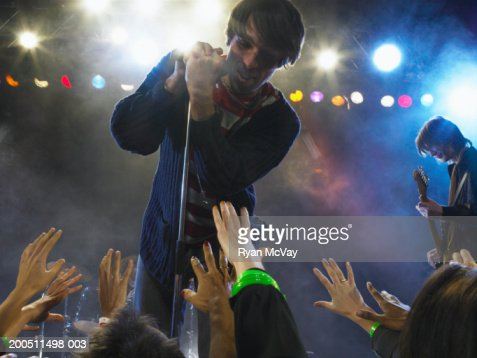 Male Singer Performing On Stage Leaning Over Audience In ...