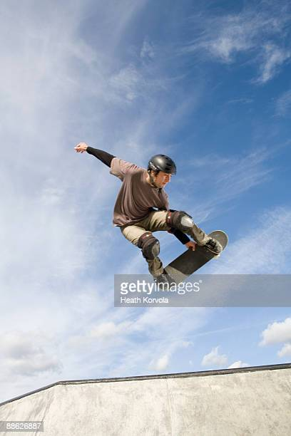 A male skateboarder catches some air.