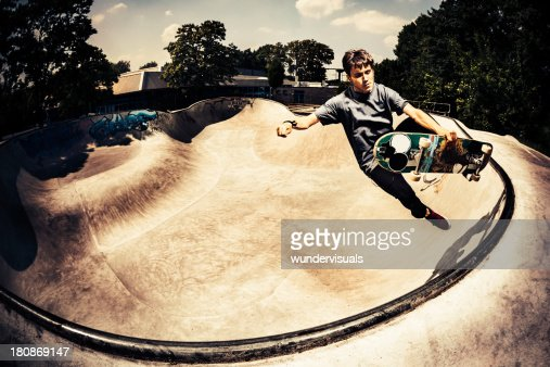 Male skateboarder grabbing his skateboard
