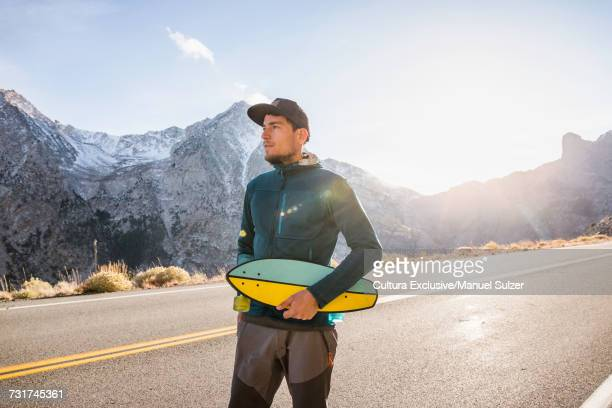 Male skateboarder looking from Tioga Pass highway in mountain landscape, Yosemite National Park, USA