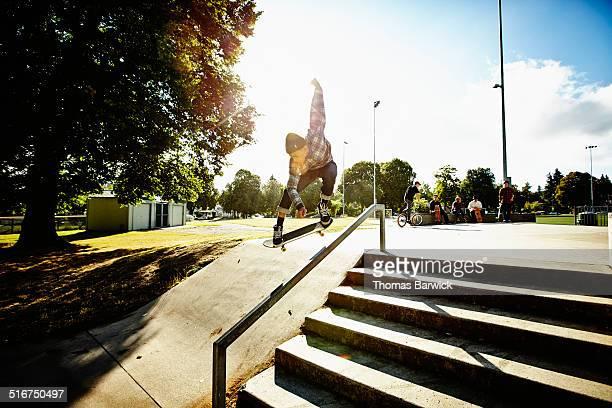 Male skateboarder ollieing over rail in skate park