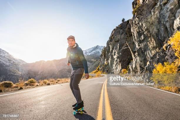 Male skateboarder skateboarding on Tioga Pass highway in mountain landscape, Yosemite National Park, USA