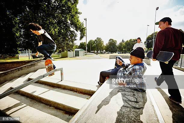 Male skateboarder taking video on smartphone